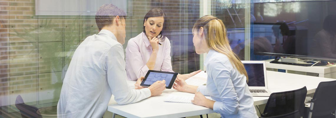 three people at conference table looking at tablet
