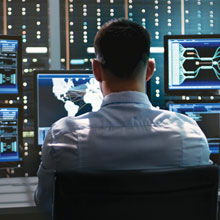 man sitting at wall of computer monitors